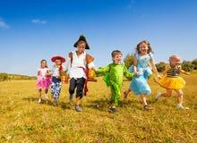 Grupo grande de niños en funcionamiento de los disfraces de Halloween Imágenes de archivo libres de regalías