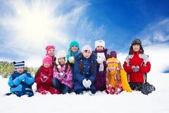 Grupo grande de niños felices que lanzan nieve imágenes de archivo libres de regalías