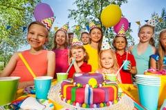 Grupo grande de niños felices que se colocan alrededor de la torta del B-día Foto de archivo