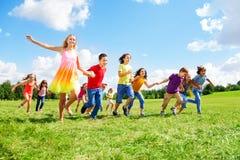 Grupo grande de niños que corren en el parque Imagenes de archivo