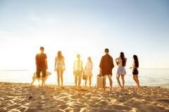 Grupo grande de playa de la puesta del sol de los amigos picknic fotografía de archivo