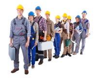 Grupo grande de trabajadores de construcción que hacen cola para arriba imagen de archivo