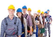 Grupo grande de trabajadores de construcción que hacen cola para arriba imagenes de archivo