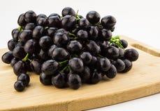 Grupo grande de uvas pretas na placa de corte de madeira Fotografia de Stock Royalty Free