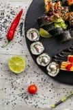 Grupo grande do sushi, a mão que guarda os hashis, a vista da parte superior Foto de Stock Royalty Free