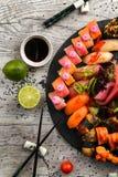 Grupo grande do sushi, a mão que guarda os hashis, a vista da parte superior Fotografia de Stock Royalty Free