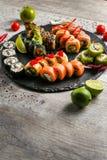 Grupo grande do sushi, a mão que guarda os hashis, a vista da parte superior Fotografia de Stock