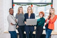 Grupo internacional de mulheres felizes que estão com retrato do portátil fotografia de stock royalty free