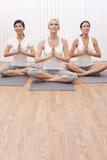 Grupo interracial de tres mujeres en la posición de la yoga Foto de archivo