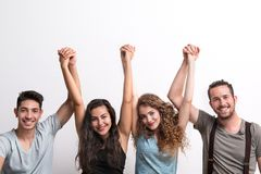 Grupo joven alegre de amigos que se colocan en un estudio, manos de elevación fotos de archivo