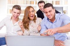 Grupo joven casual de amigos que miran y que animan junto en Fotografía de archivo libre de regalías