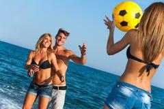 Grupo joven de amigos que se divierten con el juego de bola. Fotografía de archivo libre de regalías