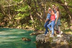 Grupo joven de amigos que se divierten en la orilla del río Foto de archivo