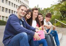 grupo joven de estudiantes que se sientan en la escalera Imágenes de archivo libres de regalías