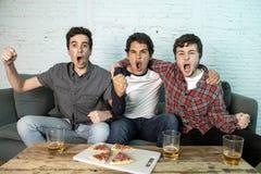 Grupo joven de hombres felices y emocionados que miran un partido de fútbol en el sofá imagenes de archivo
