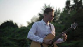 Grupo joven del inconformista de amigos que gozan junto que toca la guitarra y que canta en puesta del sol metrajes