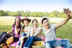 grupo joven feliz que hace el selfie por el teléfono elegante Imagen de archivo libre de regalías