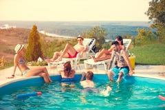 Grupo joven que goza en piscina imagenes de archivo