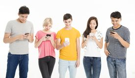 Grupo joven que mira su propio teléfono elegante Imágenes de archivo libres de regalías