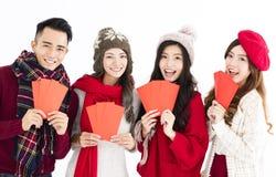 grupo joven que muestra el sobre rojo Foto de archivo