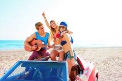 Grupo joven que se divierte en la playa que toca la guitarra Foto de archivo libre de regalías