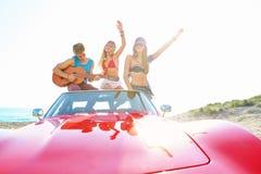 Grupo joven que se divierte en la playa que toca la guitarra Imagen de archivo libre de regalías