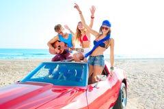 Grupo joven que se divierte en la playa que toca la guitarra Fotografía de archivo libre de regalías