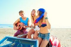 Grupo joven que se divierte en la playa que toca la guitarra Imagenes de archivo