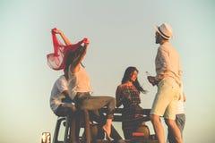 Grupo joven que se divierte en la playa y que baila en un coche convertible Foto de archivo