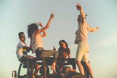 Grupo joven que se divierte en la playa y que baila en un coche convertible Imagen de archivo