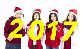 Grupo joven que se divierte y que muestra los números 2017 de la cartulina Imágenes de archivo libres de regalías