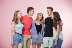 Grupo joven sonriente feliz de amigos que se colocan junto que habla y que ríe Mejores amigos imagen de archivo libre de regalías