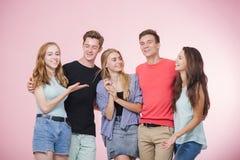 Grupo joven sonriente feliz de amigos que se colocan junto que habla y que ríe Mejores amigos fotos de archivo libres de regalías