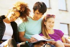 Grupo lindo de teenages en el edificio de la universidad con huggings de los libros Fotografía de archivo libre de regalías