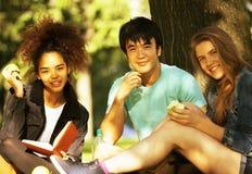 Grupo lindo de teenages en el edificio de la universidad con huggings de los libros Imágenes de archivo libres de regalías