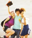Grupo lindo de teenages en el edificio de la universidad con huggings de los libros Fotos de archivo libres de regalías