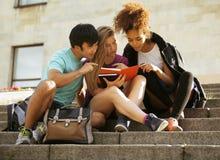 Grupo lindo de teenages en el edificio de la universidad con huggings de los libros, de nuevo a escuela Foto de archivo libre de regalías