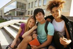 Grupo lindo de teenages en el edificio de la universidad con huggings de los libros, de nuevo a escuela Imagen de archivo