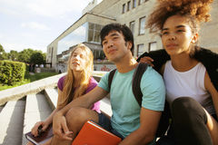 Grupo lindo de teenages en el edificio de la universidad con huggings de los libros, de nuevo a escuela Foto de archivo