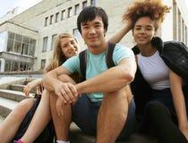 Grupo lindo de teenages en el edificio de la universidad con huggings de los libros, de nuevo a escuela Imágenes de archivo libres de regalías