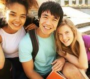 Grupo lindo de teenages en el edificio de la universidad con huggings de los libros, de nuevo a escuela Imagenes de archivo