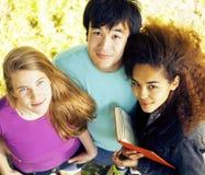 Grupo lindo de teenages en el edificio de la universidad con los huggings de los libros, naciones de la diversidad Fotografía de archivo