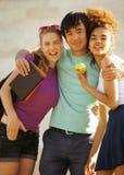 Grupo lindo de teenages en el edificio de la universidad con los huggings de los libros, naciones de la diversidad Foto de archivo