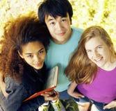 Grupo lindo de teenages en el edificio de la universidad con los libros Foto de archivo libre de regalías