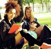 Grupo lindo de teenages en el edificio de la universidad con los libros Imagenes de archivo