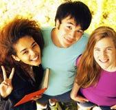 Grupo lindo de teenages en el edificio de la universidad con los libros Fotos de archivo libres de regalías