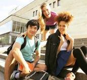 Grupo lindo de teenages en el edificio de la universidad con los libros Imagen de archivo