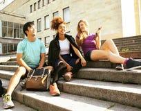 Grupo lindo de teenages en el edificio de la universidad con los libros Foto de archivo