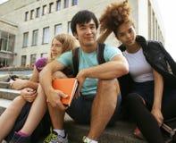 Grupo lindo de teenages en la universidad del edificio con huggings de los libros, de nuevo a escuela Imagen de archivo