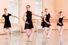 Grupo médio de adolescentes que praticam movimentos do bailado imagem de stock